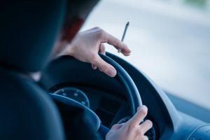 Dirigir fumando dá multa?